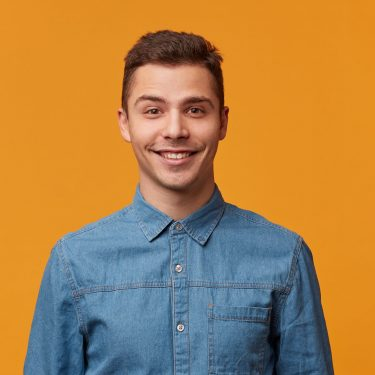 Attractive kind cute young man gently smiling dressed in a beautiful denim shirt isolated on a yellow background. Guy talking to the girl he likes.