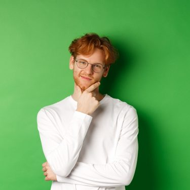 Intrigued young man with red hair, wearing glasses, looking at camera pleased and thoughtful, having an idea, standing over green background.